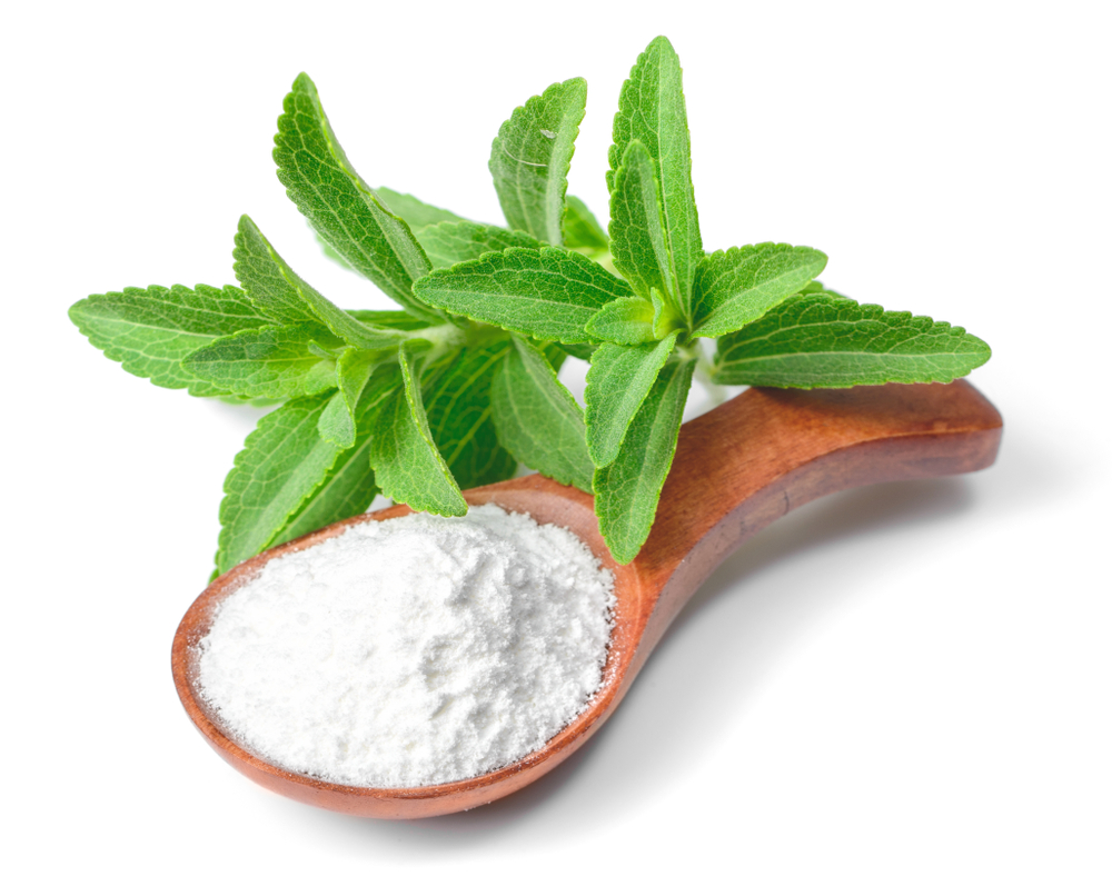 Stevia plant with white powdered stevia in a wooden spoon