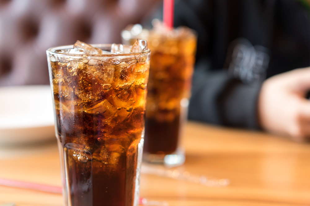 Glass of soda with ice and a straw on a table