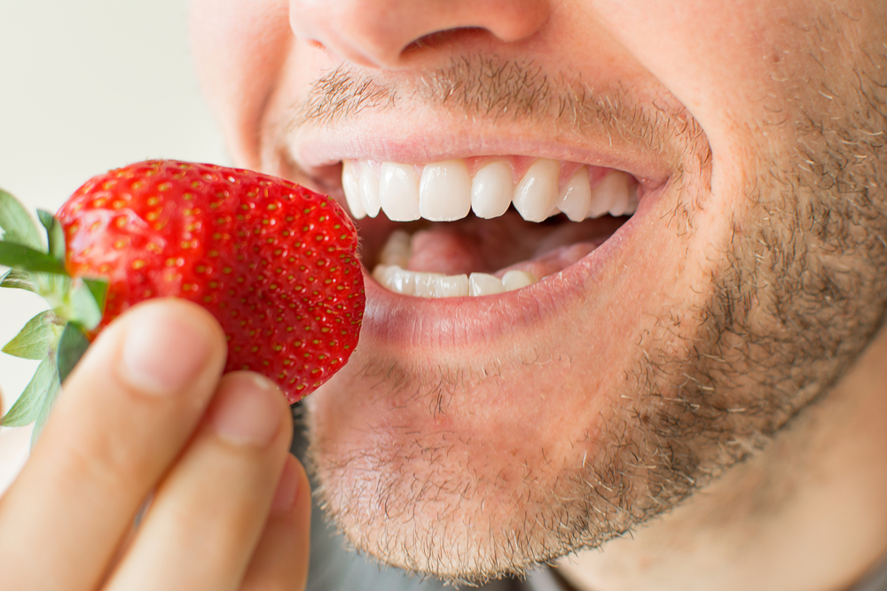 Smiling Young Man About to Eat a Strawberry