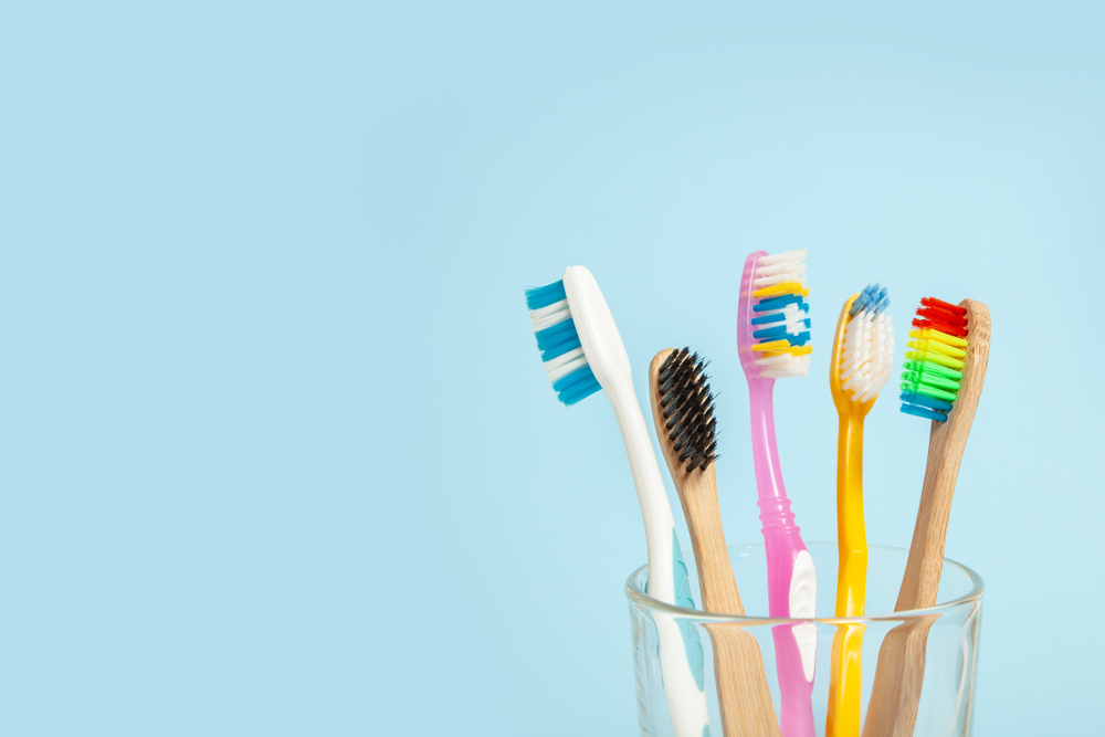 Various toothbrushes sitting in a glass