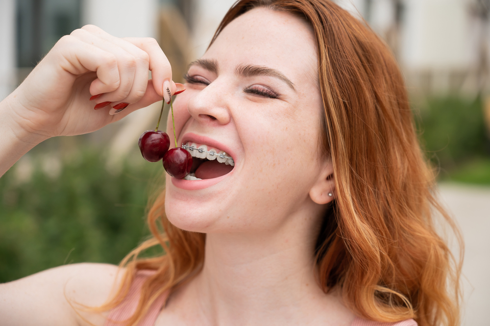 Young Woman Wearing Braces Eating Two Cherries