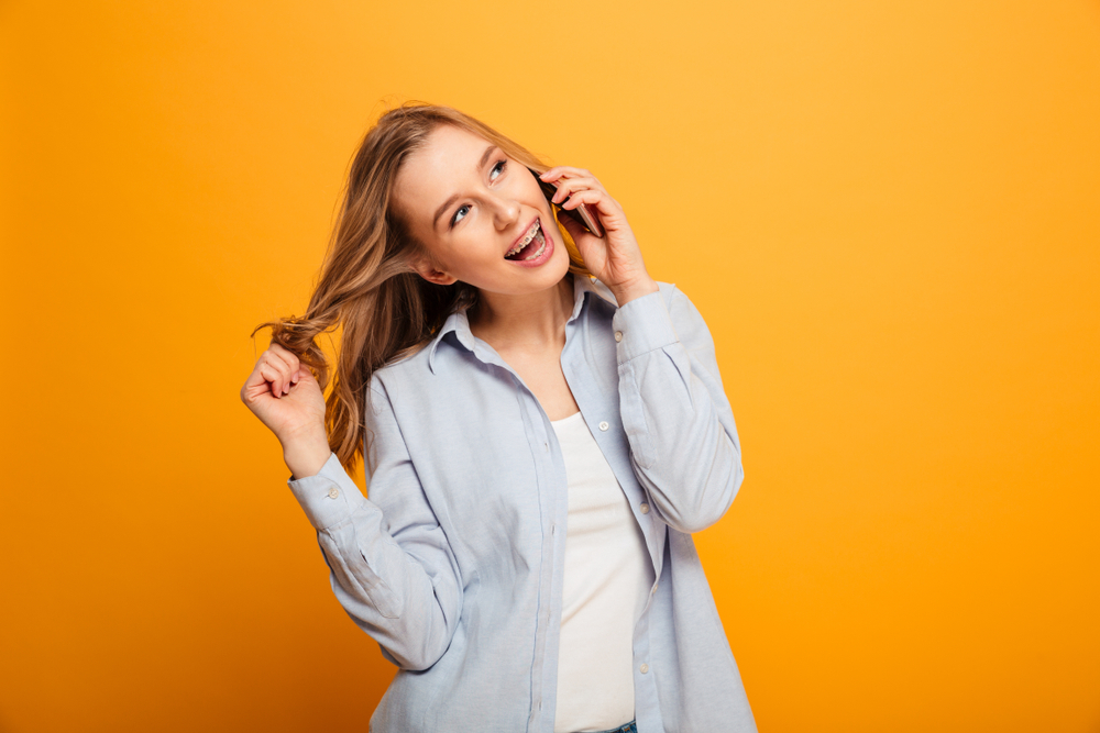 Smiling young woman with braces talking on the phone